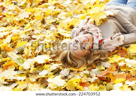 Portrait of beautiful young woman lying outdoors in autumn park - stock photo