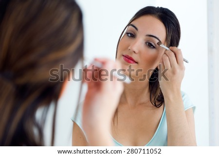 Portrait of beautiful young woman making make-up near mirror.