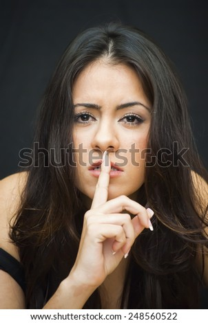 Portrait of Beautiful Young Woman making the gesture of sending silence Over Black Background