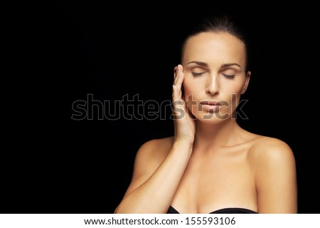 Portrait of beautiful young woman model with her eyes closed holding her hand by her face against black background. Lovely female with healthy skin. - stock photo