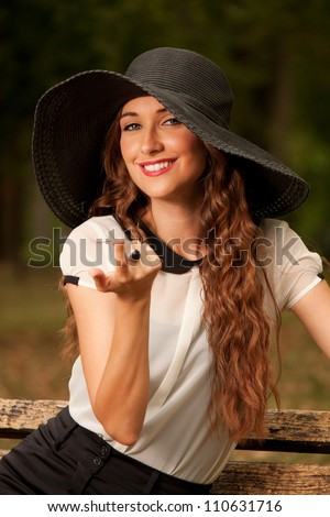 Portrait of beautiful young woman on the bench - stock photo