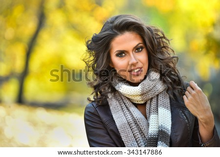 Portrait of beautiful young woman outdoors in a autumn day. - stock photo