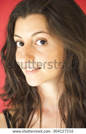 Portrait of Beautiful Young Woman Over Red Background