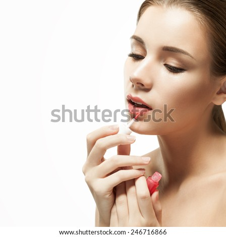 Portrait of beautiful young woman paints her lips with lipstick gloss pink,  on white background. Beauty model woman face - stock photo