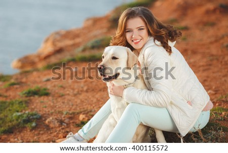 Portrait of beautiful young woman playing with dog on the sea shore. portrait of Young girl sitting on the ground with her dog retriever. woman with puppy. Girl with dog.
