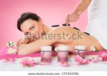 Portrait of beautiful young woman receiving hot stone therapy in spa