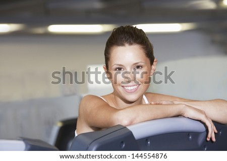 Portrait of beautiful young woman resting on treadmill at health club - stock photo