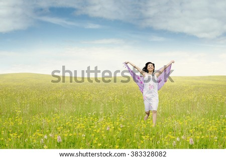 Portrait of beautiful young woman running on the meadow while holding fabric, shot at springtime