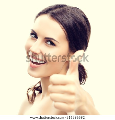 Portrait of beautiful young woman showing thumb up gesture - stock photo