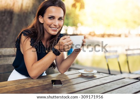 Portrait of beautiful young woman sitting at a table with a cup of coffee in hand looking at camera smiling while at cafe. - stock photo