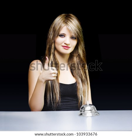 Portrait of beautiful young woman sitting at office desk giving thumbs up in a good to go sign of approval conceptual on black background - stock photo