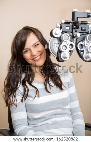 Portrait of beautiful young woman sitting behind phoropter during eye exam - stock photo