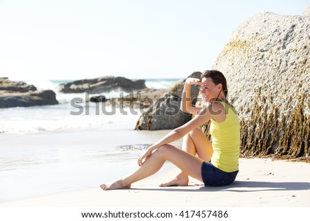 Portrait of beautiful young woman sitting on the beach and looking at sea - stock photo