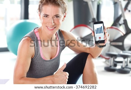 Portrait of beautiful young woman taking a break from after fitness workout and checking the daily fitness app on her mobile.  - stock photo