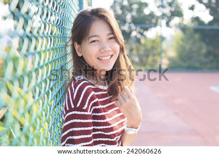 portrait of beautiful young woman toothy smiling with happy face with evening high light on hair use for happiness people and confident female  - stock photo