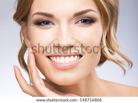 Portrait of beautiful young woman touching skin or applying cream, over grey background - stock photo