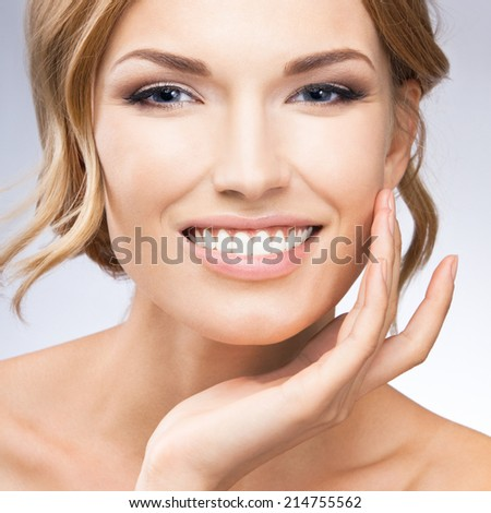 Portrait of beautiful young woman touching skin or applying cream, over grey background