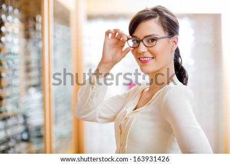 Portrait of beautiful young woman trying new glasses in optician store - stock photo