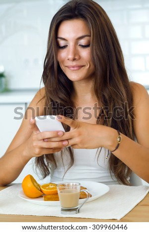 Portrait of beautiful young woman using her mobile phone and enjoying breakfast.