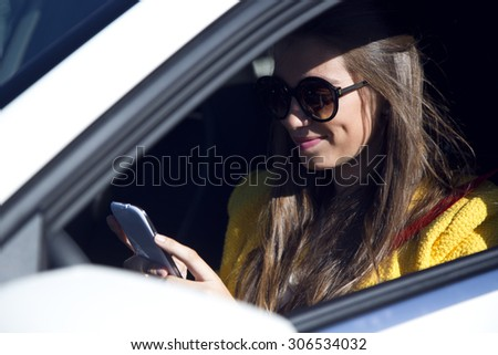 Portrait of beautiful young woman using her mobile phone in the car. - stock photo