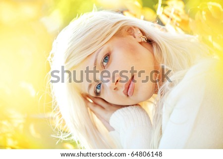 Portrait of beautiful young woman walking outdoors in autumn