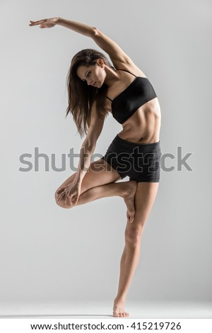 Portrait of beautiful young woman wearing black sportswear working out in studio. Fit sporty girl doing side bend exercise. Variation of Vrksasana Posture, Tree Pose. Full length. Vertical image - stock photo