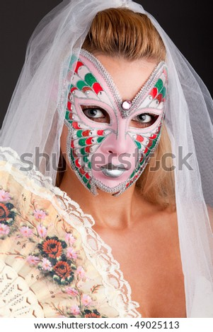 Portrait of beautiful young woman wearing carnival mask - stock photo