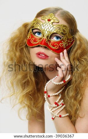 Portrait of beautiful young woman wearing gold carnival mask