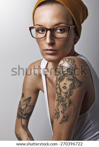 Portrait of beautiful young woman wearing hat and glasses. Tattoos all around the arms. Developed from RAW. Retouched with special care and attention. - stock photo