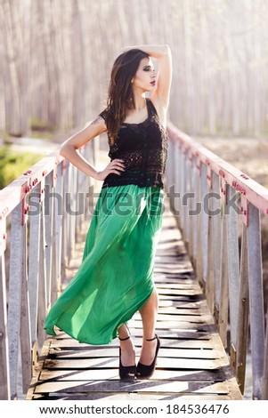 Portrait of beautiful young woman wearing long dress in a rural bridge - stock photo