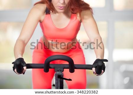 Portrait of beautiful young woman wearing red bright sportswear exercising on cycle in sports club, warming up during sport lesson in class in gym, controlling her breath, close-up - stock photo