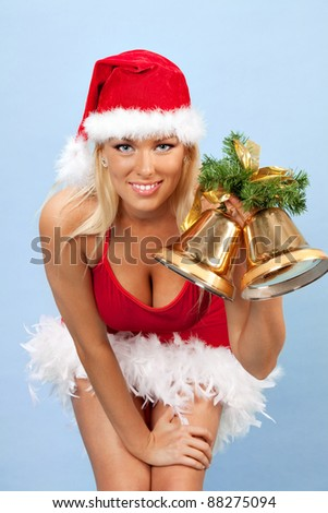 portrait of beautiful young woman wearing santa claus clothes with bells