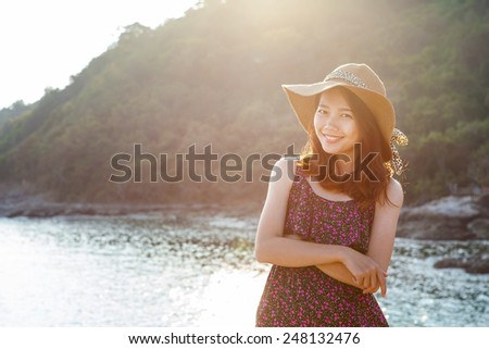 portrait of beautiful young woman wearing wide straw hat standing beside sea beach and toothy smiling face with happy emotion  - stock photo