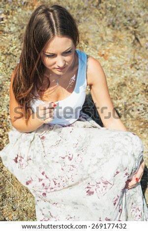 Portrait of beautiful young woman which sits on  grass on natural background. girl in a long skirt and with long hair poses in warm spring day - stock photo