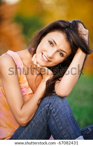 Portrait of beautiful young woman which sits on green grass in autumn garden. - stock photo