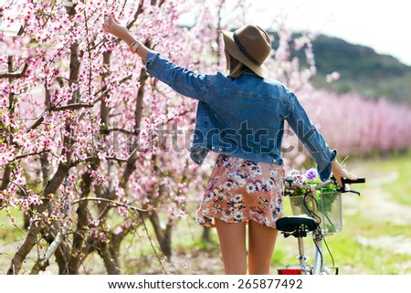 Portrait of beautiful young woman with a vintage bike in the field. - stock photo