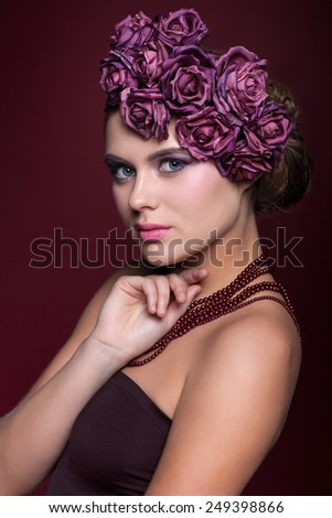 Portrait of beautiful young woman with artificial rouses on head necklace and dress on red marsala color background