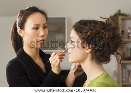 Portrait of beautiful young woman with asian esthetician making makeup - stock photo