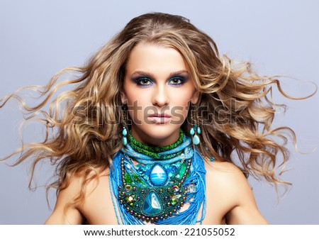 Portrait of beautiful young woman with bijouterie and fluttering hair on gray background - stock photo