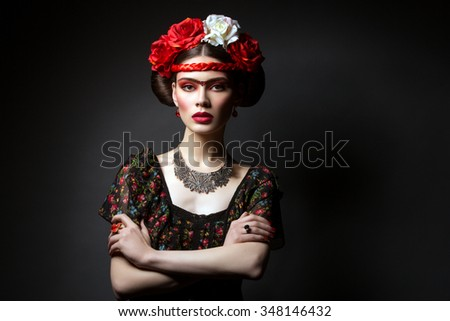 Portrait of beautiful young woman with bright red make up and roses on head. Over black background. - stock photo