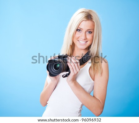 Portrait of beautiful young woman with camera on sky background - stock photo