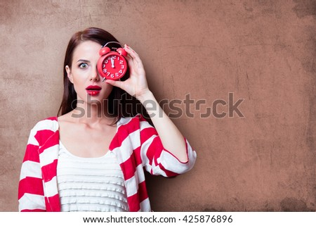 portrait of beautiful young woman with clock on the brown background - stock photo
