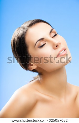 portrait of beautiful young woman with closed eyes, naked shoulders, on blue background - stock photo