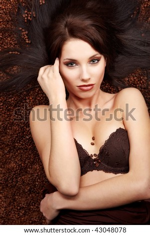 portrait of beautiful young woman with coffee beans around her