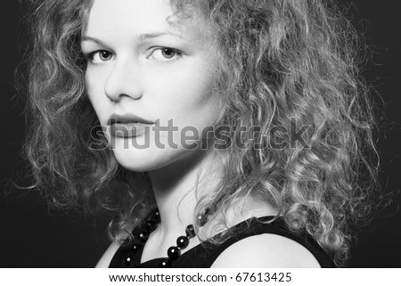 Portrait of beautiful young woman with curly hair looking at camera