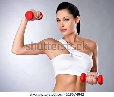 Portrait of beautiful young woman with dumbbells -  grey studio background. Healthy lifestyle concept. - stock photo