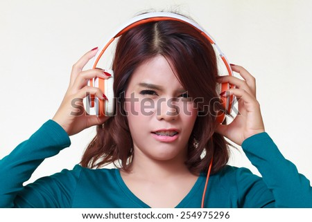 portrait of beautiful young woman with earphones listening a bad music noise - stock photo