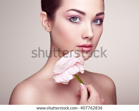 Portrait of beautiful young woman with flowers. Brunette woman with luxury makeup. Perfect skin. Eyelashes. Cosmetic eyeshadow - stock photo
