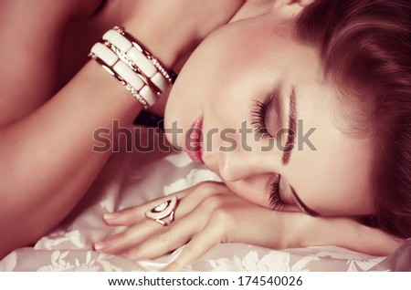 Portrait of beautiful young woman with golden jewelry on black background - stock photo
