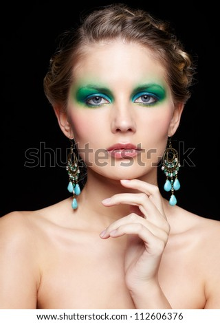 portrait of beautiful young woman with green and blue eye shade make-up touching her chin